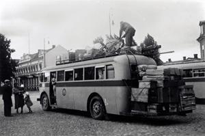Buss med mycket bagage på taket och baktill