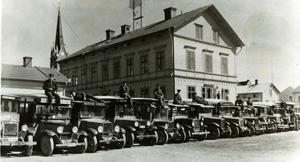 Uppställda 1920-talsbussar med förare på taket